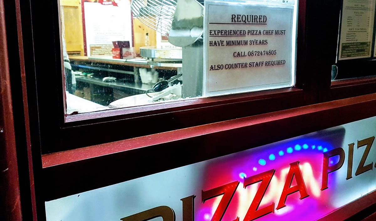 Pizza sign with back-lit flashing open sign style lighting - window into an Irish pizzeria