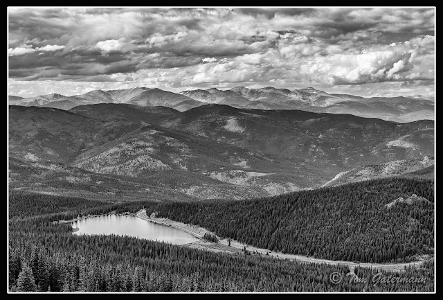 A black and white photographic view from Mount Evans Road, of Lake Echo set against the vast mountains and sky.