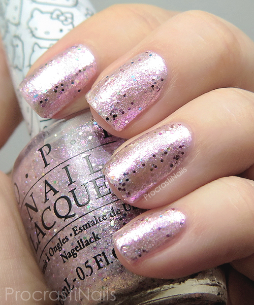 Swatch of OPI Charmmy & Sugar a sheer pink iridescent metallic microflakie glitter with scattered multi-coloured hex glitter