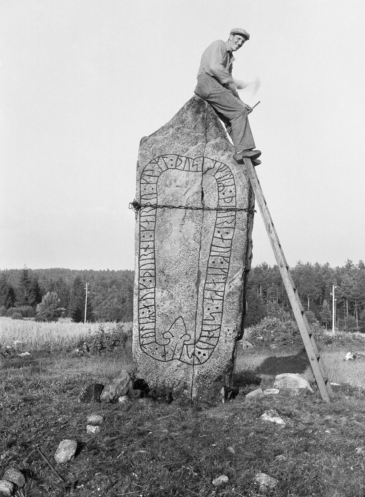 A man works on restoring a cracked runestone at Svedjorna in Södra Ving. The inscription reads,