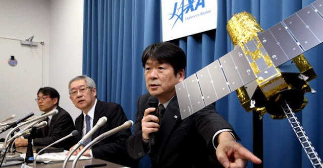 Chikara Harada, right, head of the Space Tracking and Communications Center of the Japan Aerospace Exploration Agency (JAXA), responds to a question in a news conference in Tokyo on April 28 while using a model of an X-ray astronomy satellite Hitomi. Next to him is Saku Tsuneta, director of JAXA's Institute of Space and Astronautical Science. (Wataru Sekita)