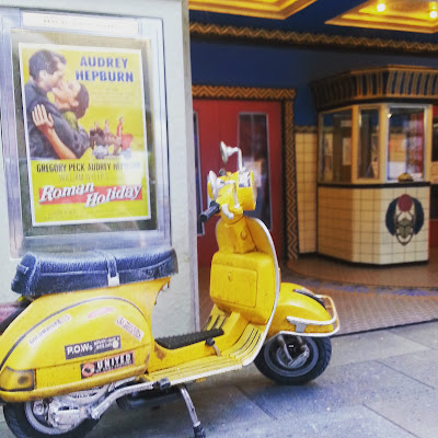 Modern dolls' house Vespa scooter parked in front of a cinema lobby.