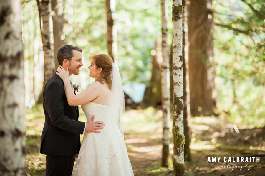 bride and groom smiling at each other in thick forest