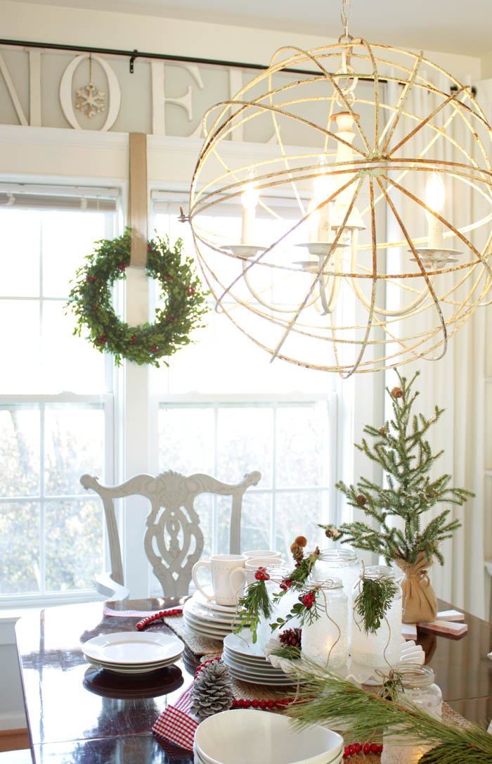 sphere chandelier, red wooden bead garland, pinecones, white dishes