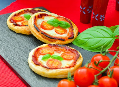 Mini Margherita Puff Pizzas on a slate board with on the vine tomatoes and fresh basil