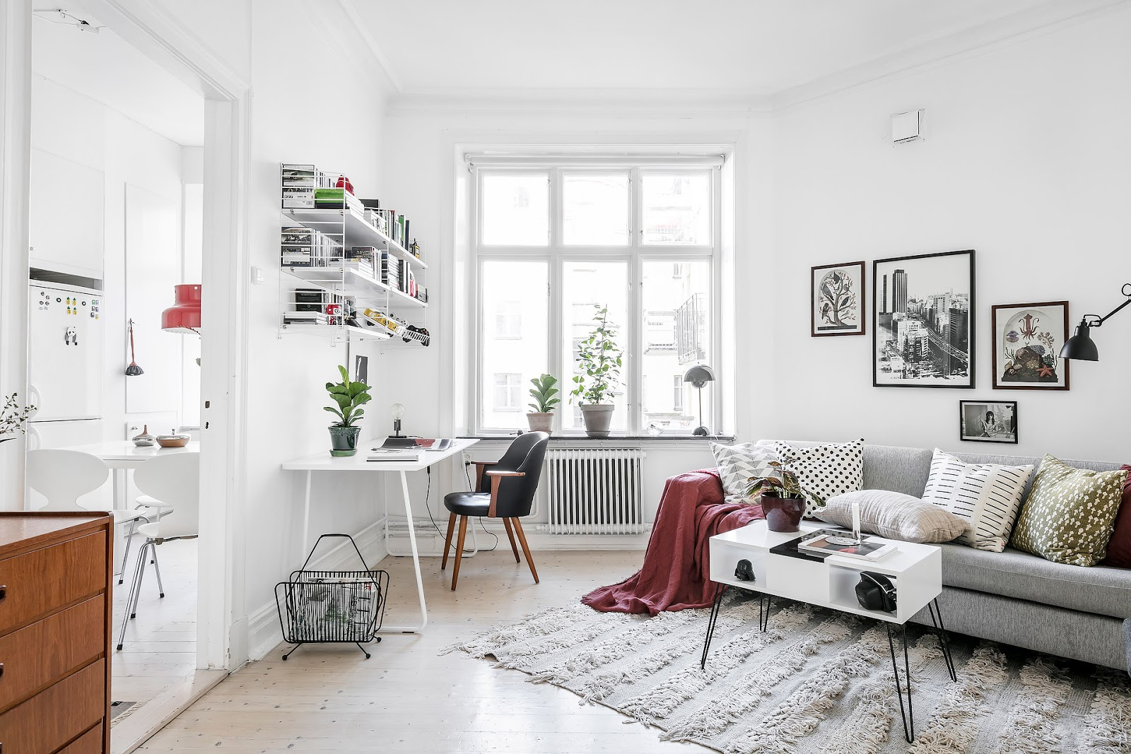 small Scandinavian apartment, gray Ikea sofa with pattern printed pillows, black Panton lamp, componobili by kartell