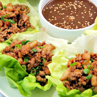 Closeup of Copycat PF Chang's Chicken Lettuce Wraps on a white serving platter with dipping sauce in a white bowl.