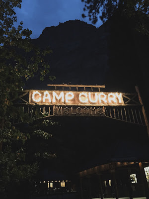 A picture of the Camp Curry sign lit up at night in Yosemite National Park
