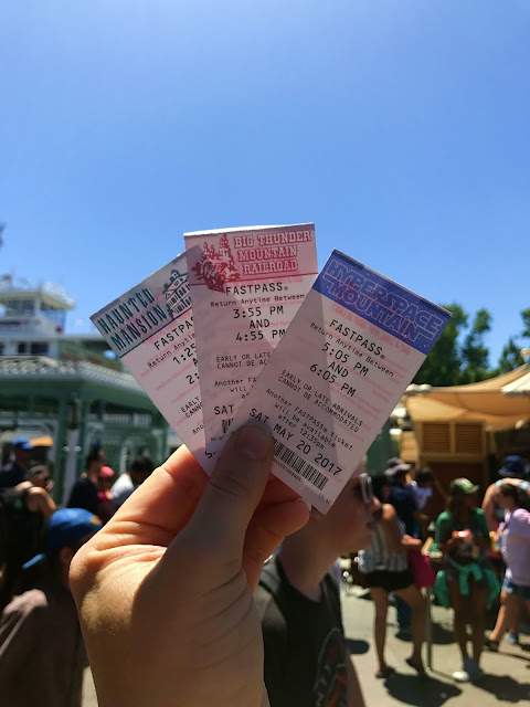 Holding up paper fastpass tickets at Disneyland for Big Thunder Mountain, Haunted Mansion and HyperSpace Mountain
