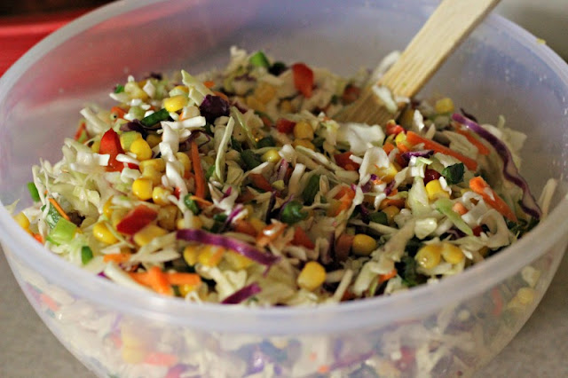 Firecracker Coleslaw by Renee's Kitchen Adventures mixed up in a white bowl with a serving spoon