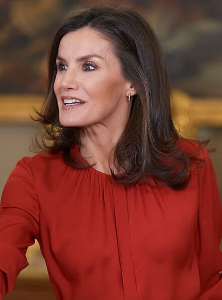 Queen Letizia wore Hugo Boss Banora red gathered neck silk blouse and Carolina Herrera black poppy-print knit skirt, gold diamond earrings
