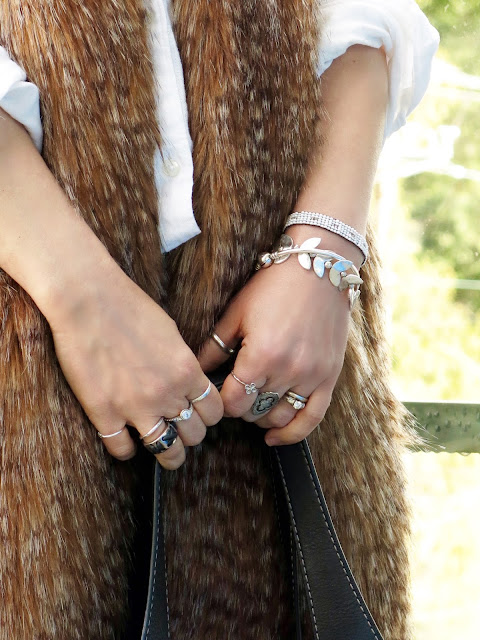 white shirt with a long, faux-fur vest and stacked bracelets and rings
