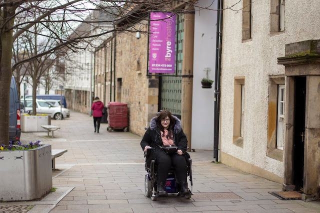 Woman sat in powerchair outside Byre Theatre in St Andrews, she's wearing black coat, black jeans and pink hoody