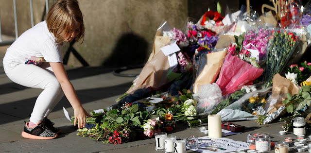 A girl leaves flowers for victims of an attack at Manchester Arena