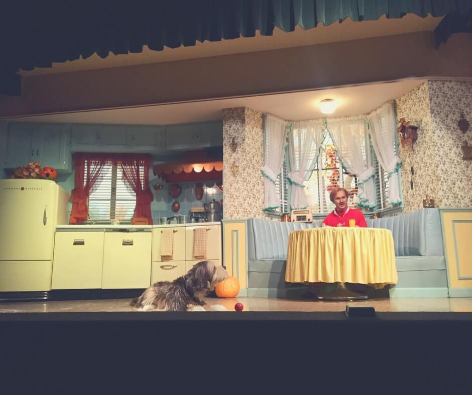 "An animatronic man sits at a cloth covered kitchen table waving a fan. The kitchen is decorated in 1940s style with orange curtains hanging at the windows behind the man. A large hairy dog sits on the floor in front of the table looking up at his owner. The photo was taken from inside Carousel of Progress. Image for ""How to get a much-needed rest at Magic Kingdom""."