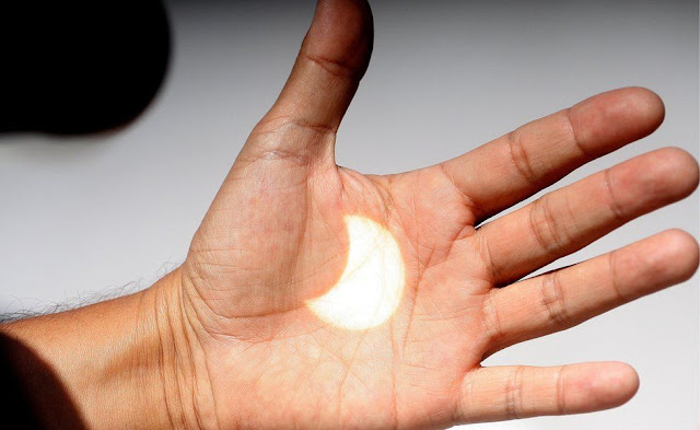 Một cách quan sát nhật thực khác, để hình ảnh Mặt Trời bị Mặt Trăng che khuất qua kính quan sát chiếu vào lòng bàn tay. Hình ảnh: EPA.
