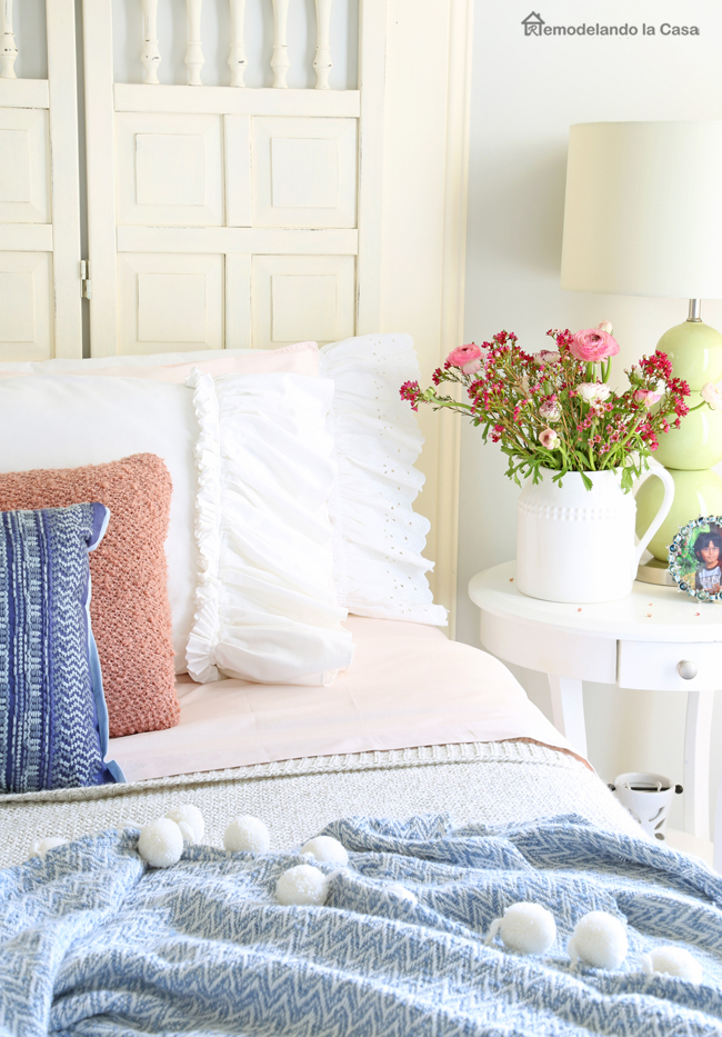 Bedroom decor with pink sheets, sweater knit blanket and white ruffled pillow covers on a bed with wooden headboard