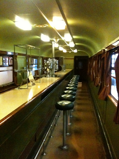 The interior of the Great western buffet car, with a long shiny counter stretching the length of the coach, and a row of little round stools in front.