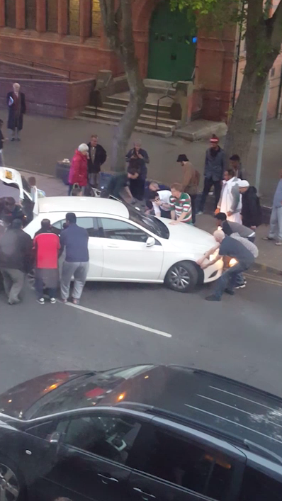 Amazing moment 15 passers-by LIFT Mercedes A Class off a seven-year-old boy after road crash