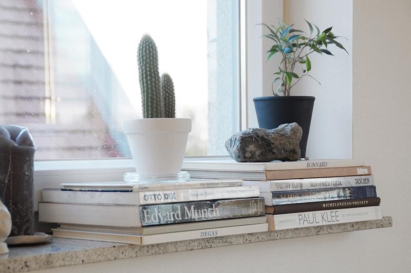 Fensterbank dekorieren mit Bildbänden, Zimmerpflanzen und Objekten in schwarz-weiß