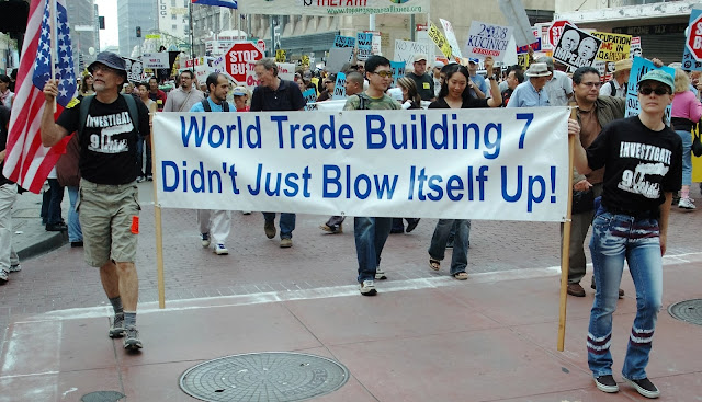 "Protesters in New York City carry saying ""World Trade Center Building 7 didn't just blow itself Up!"""