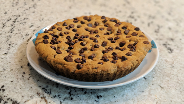 image of a chocolate chip cookie cake sitting on a plate on my kitchen counter