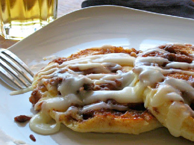 cinnamon roll pancakes on a white plate with fork