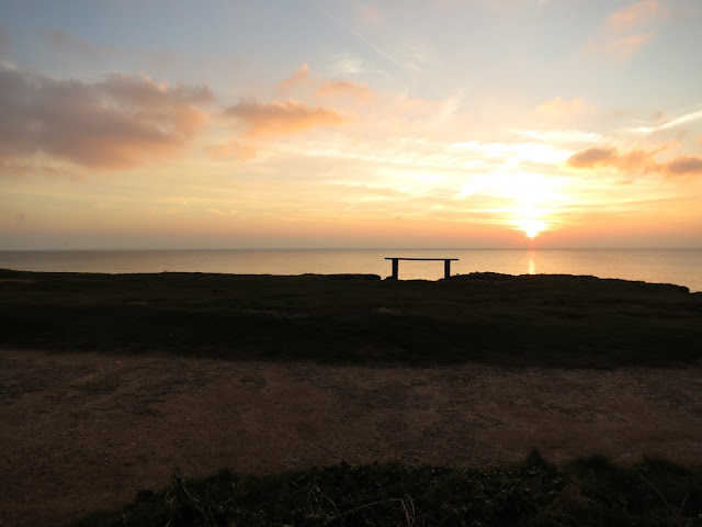 Bench with sea at early sunset, Burton Bradstock, Dorset