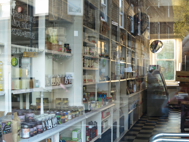 Looking through shop windows. Reflections from within shop and in round mirror.AC