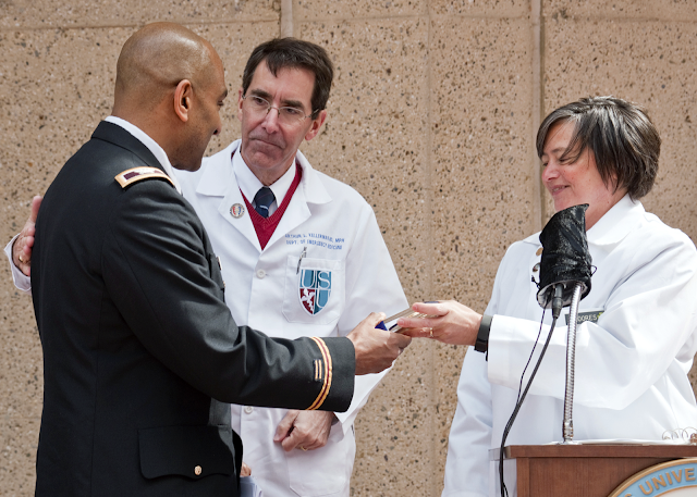 Two people in white coats congratulating a man in military dress