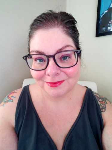 image of me from the shoulders upward, sitting in my desk chair with my hair up, wearing a grey tanktop and gray-framed glasses, with pink-themed makeup