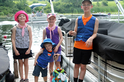 Four kids at a river wearing Cool Kids cooling vests and cooling neck wraps