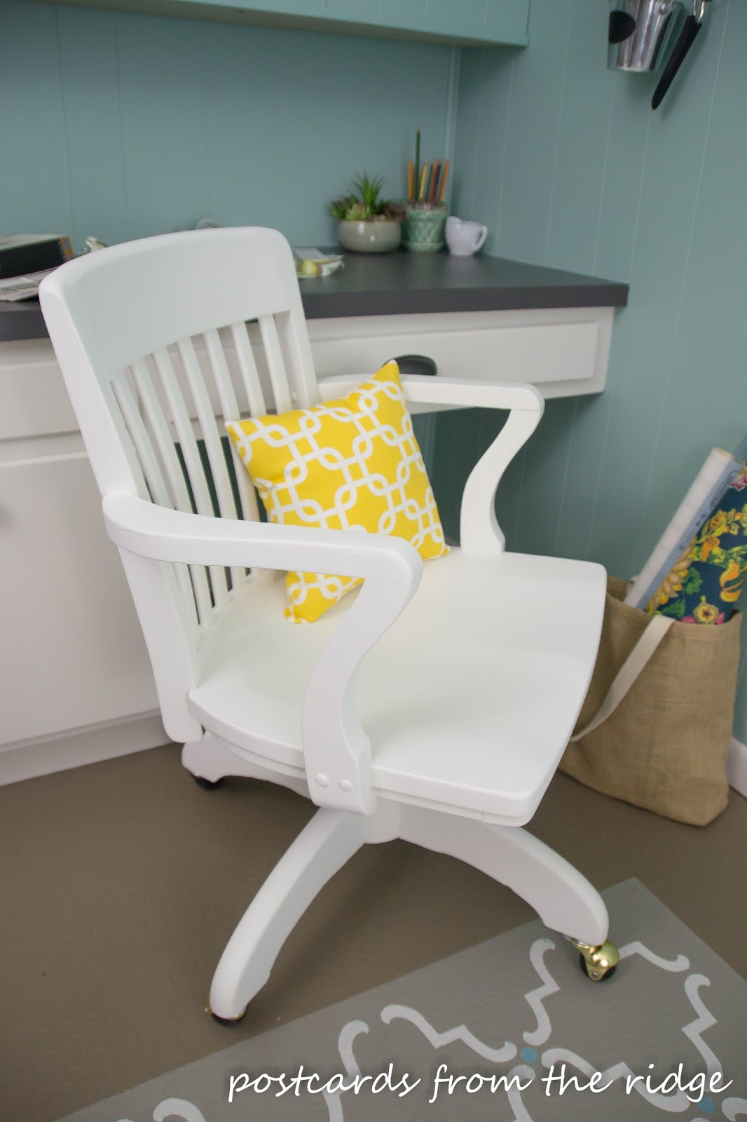 An old wooden swivel office chair gets a facelift with a new pillow, fresh white dove paint, and new caster wheels.