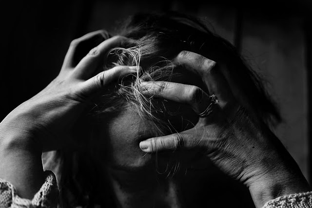 stock photo for depression from pexels.com - black and white photo of a woman with head in hands.