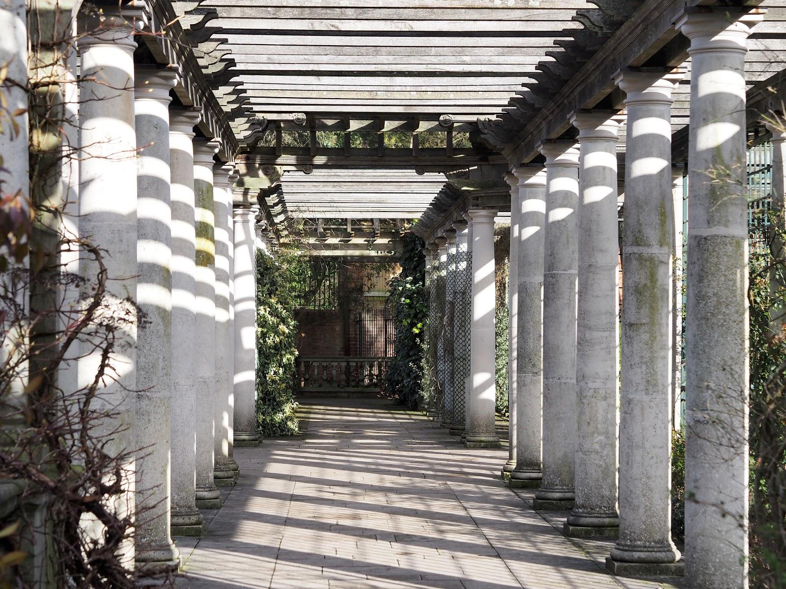 pillars with the sun shining though on Hampstead Heath