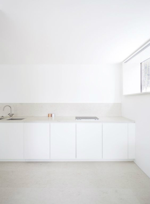 Küche mit schlich-weißer Zeile und einem Boden und Arbeitsplatte aus hellem Stein.