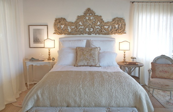 Romantic farmhouse European inspired bedroom with architectural element above bed by Giannetti Home