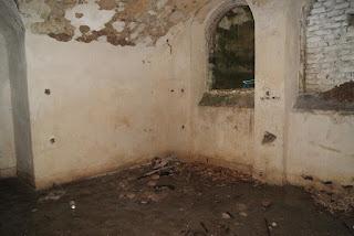Ein offenes Rundbogenfenster, durch das es geregnet hat. Der Boden vor dem Fenster ist mit Schutt und Schlamm bedeckt