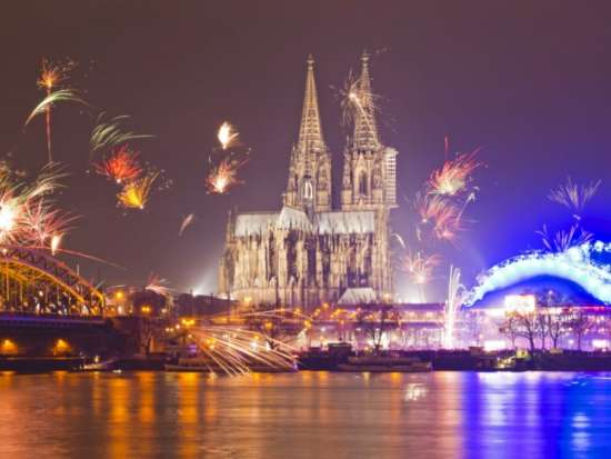 Dom of Cologne (Koeln) on New Year's Eve with fireworks on display in the background