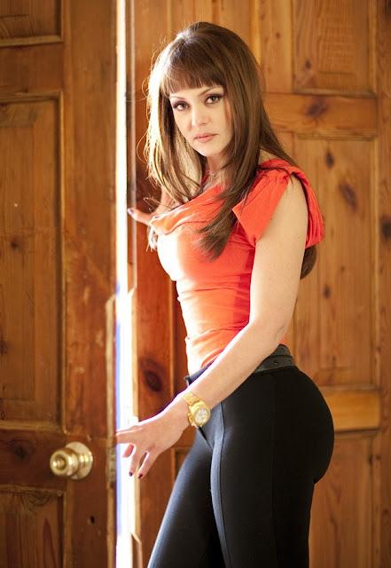 Ivana com blusa laranja colada e calça preta colada, ela está perto da porta entre aberta e usa um relógio no pulso de ouro