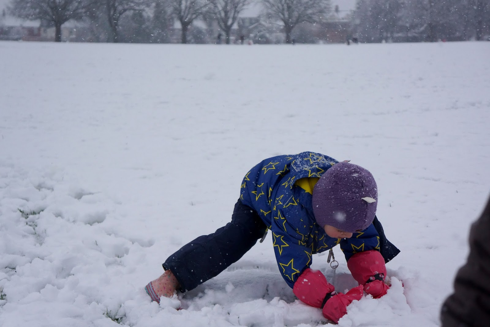 girl rolling a snow ball