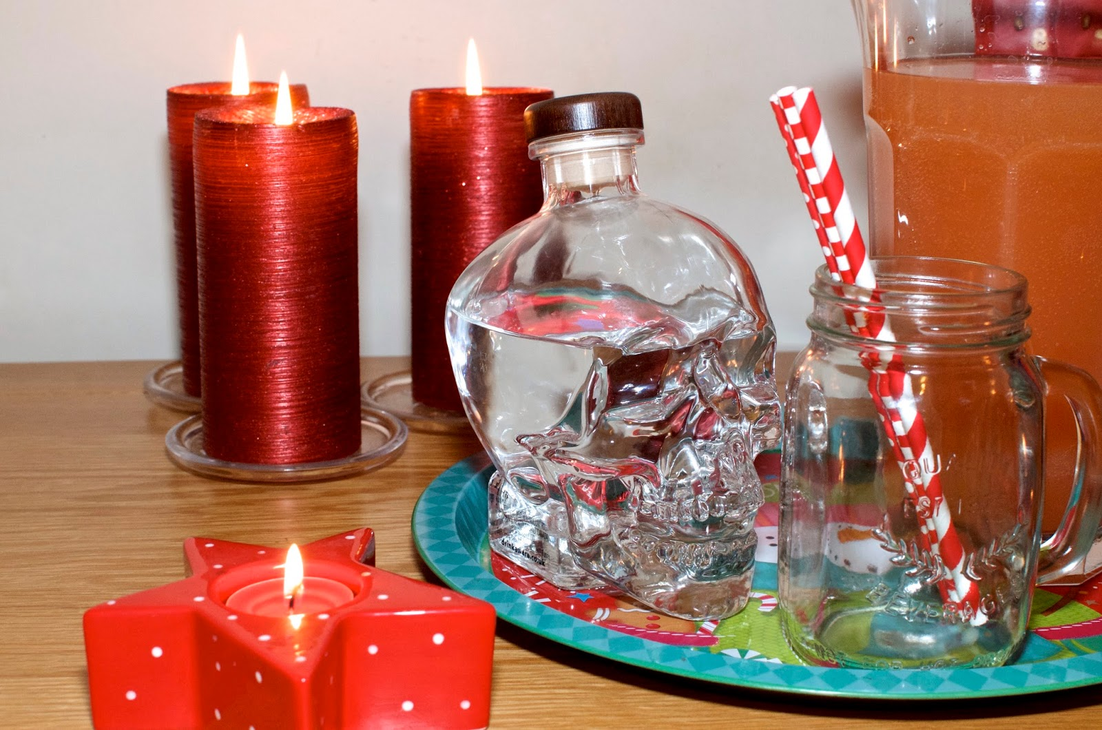 Crystal Skull Vodka Bottle, red candles, straws, jam jar glass and pink punch
