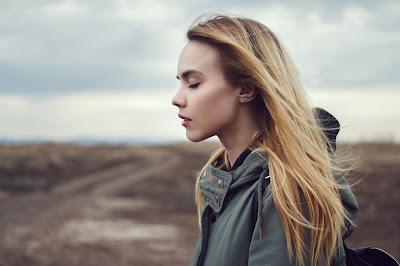 Chica rubia con los ojos cerrados y tierra de fondo