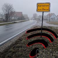 Ortseingangsschild Karlskron mit WLAN-Symbol im matischgen Seitenstreifen