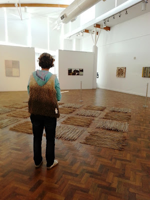 A woman standing in front of work at The Daylight Moon: an exhibition of Rosalie Gascoigne's  work, showing at Goulburn Regional Art Gallery.