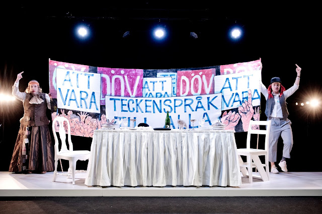 "Actors Joakim Hagelin Adeby and Mette Marqvardsen on stage, standing behind the table holding up a banner that reads, in Swedish: ""TO BE. DEAF. SIGN LANGUAGE FOR ALL."" Photographer: Urban Jörén"