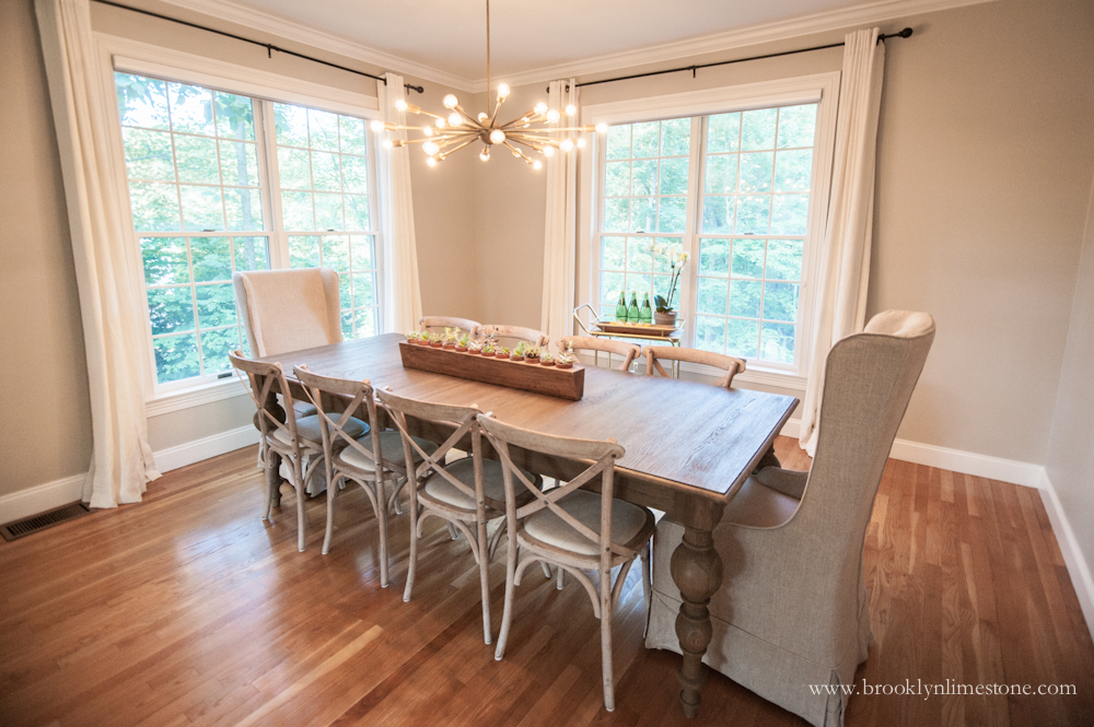 Dining room with cream curtains on 2 double hung windows, new grey wood table with upholstered cream end chairs and 3 cross backed chairs on each side