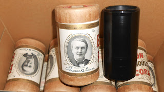 A photograph of a pile of wax cylinders.