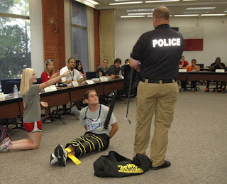Student bound in restraining device by University Police Department officer.
