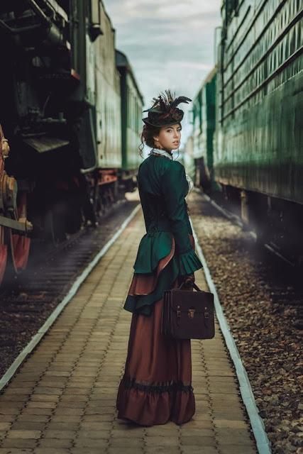 Woman wearing victorian steampunk clothing in green and brown, standing next to a steam train. Women's steampunk fashion.